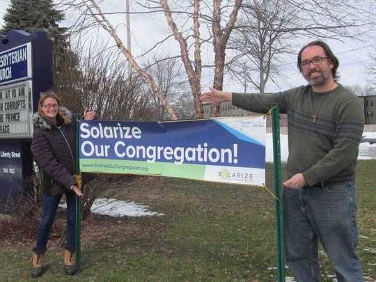 The Rev. Ben Larson-Wolbrink, right, of the First Presbyterian Church in Beacon holds a banner supporting the Solarize Our Congregation initiative.