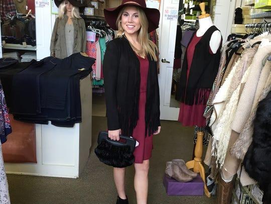 A black fringe jacket and burgundy floppy hat. Holiday
