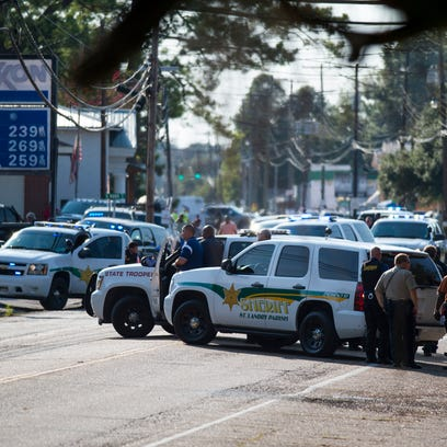 Police line the street on Napoleon Avenue in Sunset,