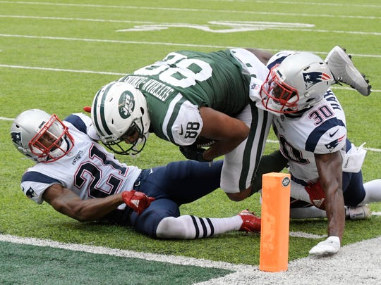 New York Jets tight end Austin Seferian-Jenkins (88) is tackled by New England Patriots' Malcolm Butler (21) and Duron Harmon (30) during the second half of an NFL football game Sunday, Oct. 15, 2017, in East Rutherford, N.J. After further review the play was ruled a fumble into the end zone.