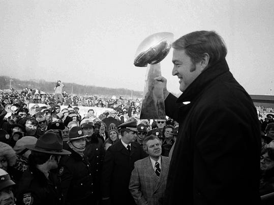 FILE - In this Jan. 13, 1975, file photo, Pittsburgh Steelers coach Chuck Noll holds Super Bowl trophy aloft before fans who greeted the team at the airport in Pittsburgh on the team's return from New Olreans. The Steelers won the first NFL football title in their 42 year history by defeating the Minnesota Vikings in Super Bowl IX. Noll, the Hall of Fame coach who won a record four Super Bowl titles with the Steelers, died Friday night, June 13, 2014, at his home. He was 82. The Allegheny County (Pa.) Medical Examiner said Noll died of natural causes. (AP Photo, File)