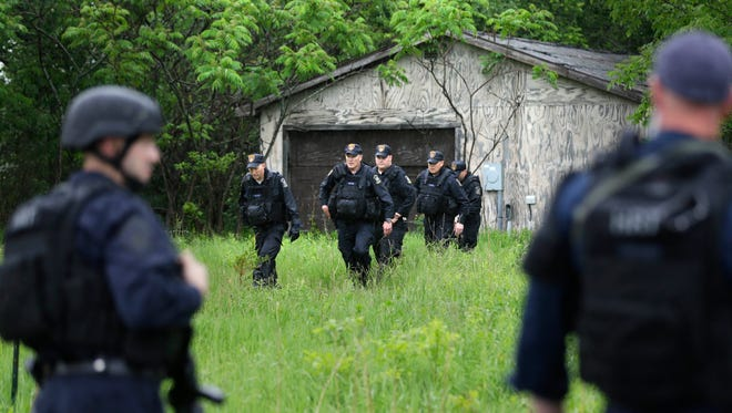 Law enforcement officers search for escaped prisoners near Essex, N.Y., Tuesday, June 9, 2015. State and federal law officers searching for two killers who used power tools to break out of a maximum-security prison poured into a small town 30 miles away Tuesday after getting a report of a possible sighting. (AP Photo/Seth Wenig)