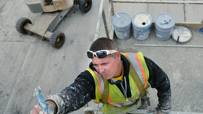 Domenic Rolak of G and M Painting paints the Berwyn Street bridge in Redford.