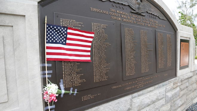 A small US flag and flowers taped to the memorial dedicated to all from Tippecanoe County who have made the supreme sacrifice in defense of the country next to Memorial Island Friday, May 27, 2016, in Columbian Park.
