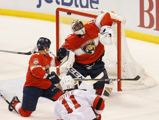 Florida Panthers goaltender Roberto Luongo (1) defends as the puck misses while New Jersey Devils center Brian Boyle (11) and Panthers center Micheal Haley (18) watch during the second period of an NHL hockey game Thursday, March 1, 2018, in Sunrise, Fla. (AP Photo/Joe Skipper)