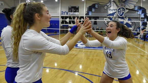 St. Joseph's junior Kyra Thompson, left and sister Kimmie Thompson, an eighth-grader, exchange high-fives before Monday's match against Gray Collegiate Academy. St. Joe's won 3-0 to claim its seventh straight Upper State title.