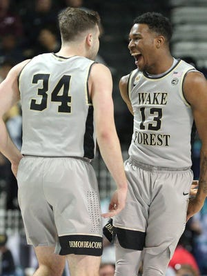 Wake Forest Demon Deacons guard Bryant Crawford (13) celebrates with Wake Forest Demon Deacons forward Austin Arians (34) during the first half of an ACC Conference Tournament game against the Boston College Eagles at Barclays Center.