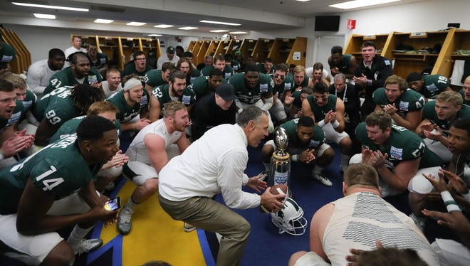 Michigan State coach Mark Dantonio and his team celebrate in the locker room after MSU's 42-17 win over Washington State in the San Diego County Credit Union Holiday Bowl on Thursday, Dec. 28, 2017, in San Diego.