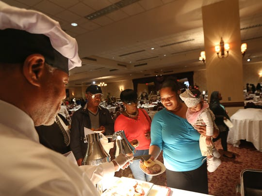 William Clark, President and CEO of the Urban League of Rochester, serves up his Southern Style Honey Glazed Ham to his daughter, Shauna Clark, Perinton, and granddaughter Raina Powe, 11 months, in 2015.