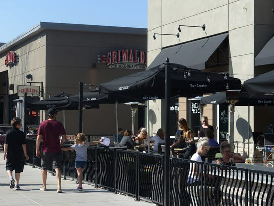 Pedestrians pass by the patio at Bar Louie at the Foothills shopping center in Midtown Fort Collins on Wednesday, April 12, 2017. Sales tax collections at Foothills continue to be strong, bucking a softening of city tax collections in the first three months of 2017.