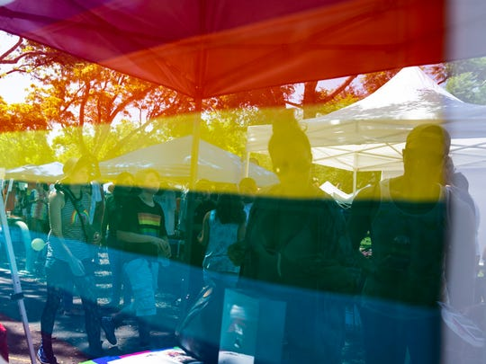 Attendees walk past an original Gilbert Baker flag, signed and numbered 3 of 20, on display during the second annual Naples Pride at Cambier Park on Saturday, June 2, 2018.