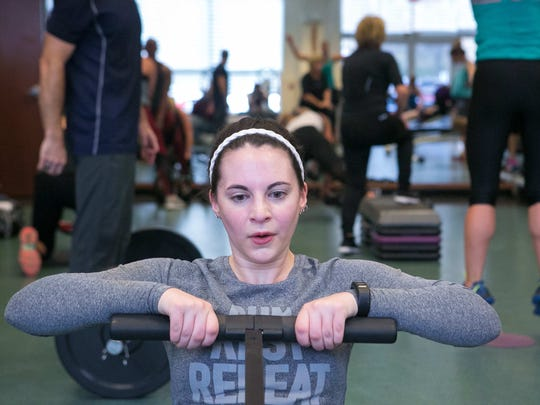 Health reporter Jen Rini on the rowing machine taking a deep breath as she participates in a high intensity small group personal training class at Hockessin Athletic Club.