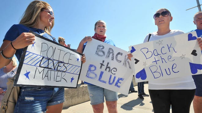 Cherilyn Paradis, left, joins Karen Cyr, center, and Jackie Flynn, all of Quincy, during the pro-police rally at Wollaston Beach in Quincy on Saturday, June 20, 2020. Tom Gorman/For The Patriot Ledger
