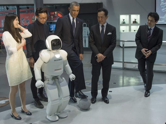 President Barack Obama positions a soccer ball as he talks with Honda's humanoid robot ASIMO, an acronym for Advanced Step in Innovative MObility, student Nao Yamamoto (L), student Iida Satoru (2nd L) and chief executive director of the Miraikan Museum, Mamoru Mohri (2nd R), as he tours the Miraikan Science Expo in Tokyo on April 24, 2014.