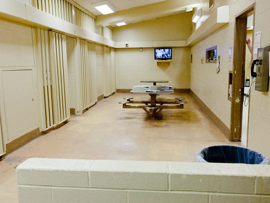 A cell block at the Tompkins County jail with individual jail cells, left, and a common living area, center, in the Tompkins County Jail.