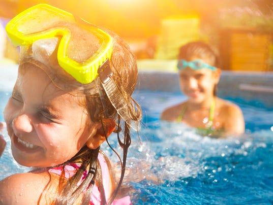 Children playing in pool. Two little girls having fun