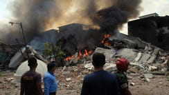 Indonesian rescuers stand near a crashed military airplane