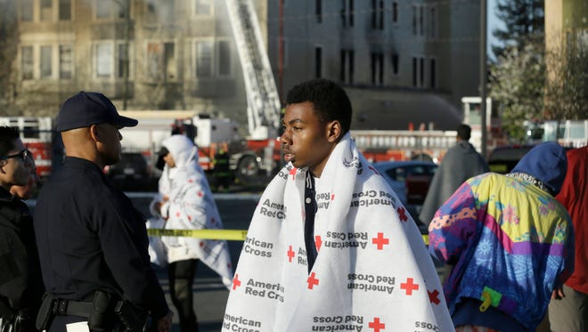 An evacuee waits as firefighters battle an apartment fire March 27, 2017, in Oakland.