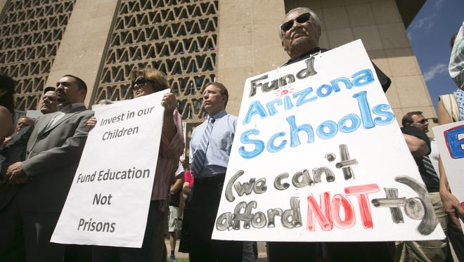 Carolyn O'Connor (left) and Tony Bracamonte, both of the East Valley Patriots for Social Justice, hold signs while rallying for better education funding in front of the state Capitol on Sept. 3, 2015.