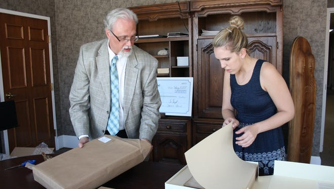 Customs House Director Jim Zimmer and Curator of Collections Kali Mason look over the newly restored Civil War journal of Serepta Jordan, discovered in a Smoke House in New Providence and added to the Museum's collection in 1984.