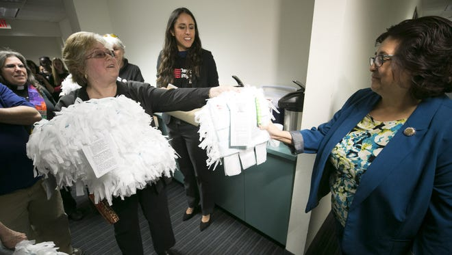Dede Durkee (left) of Fountain Hills, hands out pillows made of feminine products to Arizona Rep. Rosanna Gabaldon, (D-Green Valley) to raise awareness about issues facing incarcerated women at the Arizona State House in Phoenix.