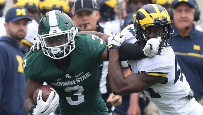 Michigan State Spartans halfback LJ Scott takes on Michigan Wolverines safety Delano Hill on Saturday, Oct. 29, 2016 at Spartan Stadium in East Lansing.