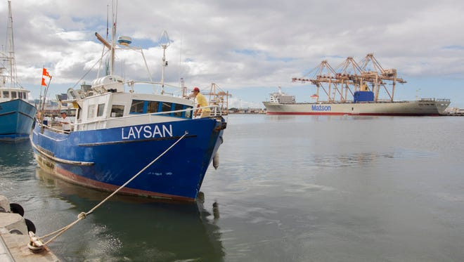 A fishing boat docks at Honolulu Harbor, where more than 26,000 fish and other marine species suffocated and died as the molasses leaked in the harbor this year.