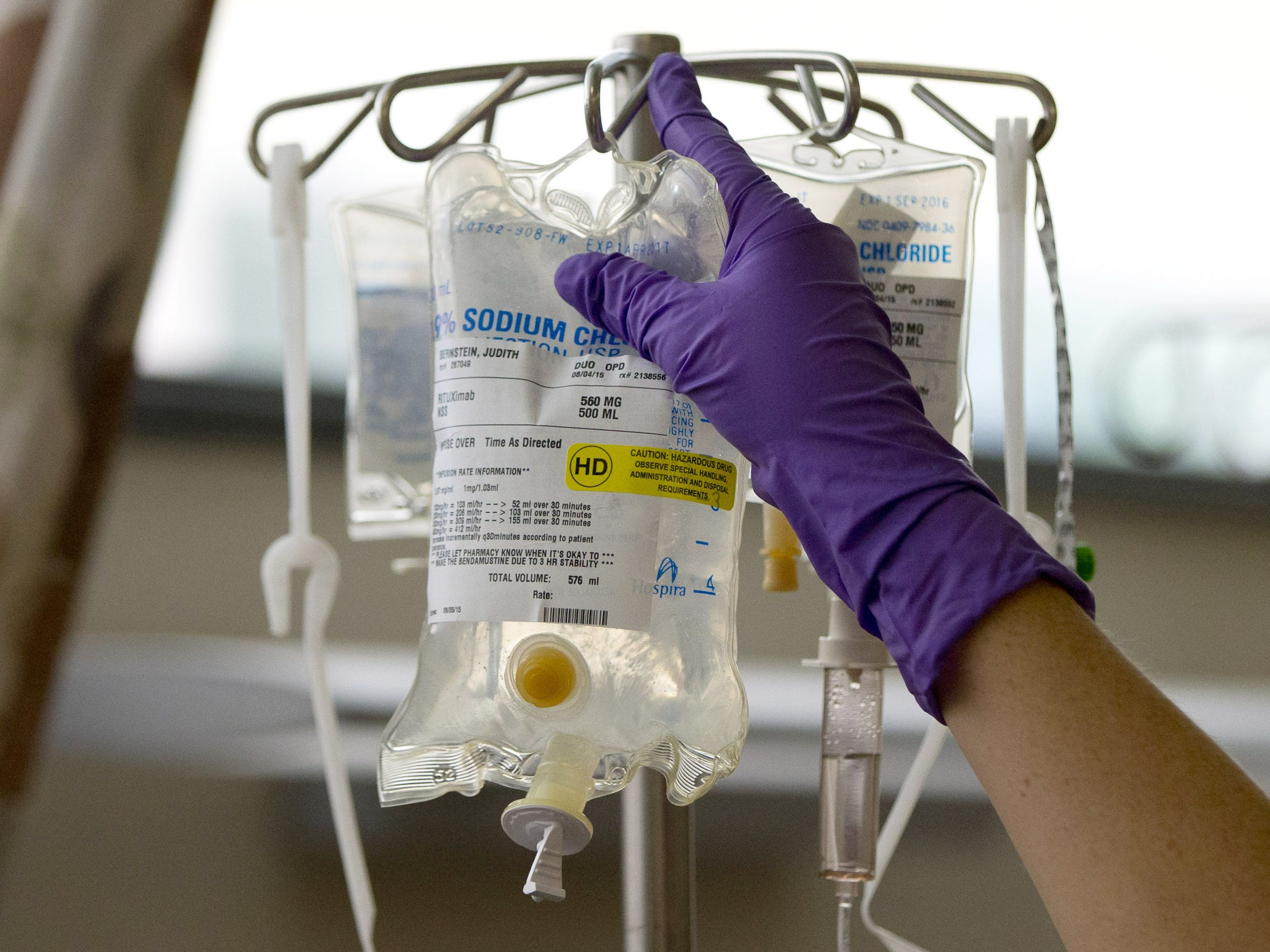 In this file photo, a nurse places chemotherapy medication on an intravenous stand at a hospital.