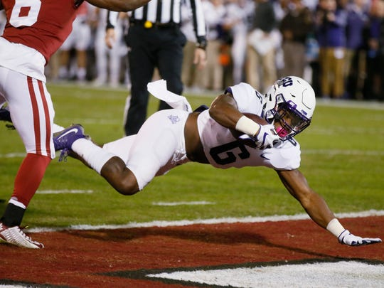 TCU running back Darius Anderson (6) dives into the end zone for a touchdown in front of Oklahoma defender Tre Brown, left, in the first quarter of an NCAA college football game in Norman, Okla., Saturday, Nov. 11, 2017. (AP Photo/Sue Ogrocki)