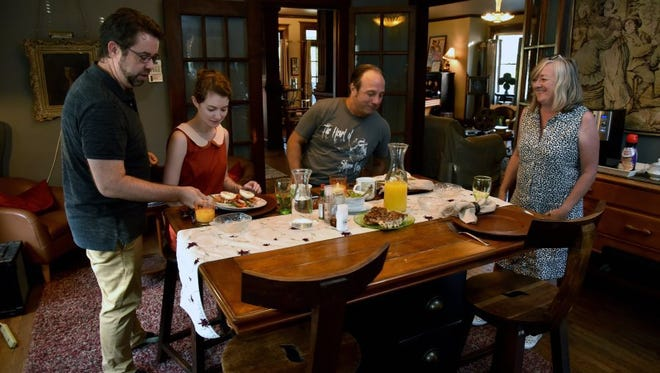 Doug McDaniel, left, serves breakfast to Laura Webb and Michael Benton on Aug. 3, 2016. Faith McDaniel, right, prepared the eggs Benedict for the guests of the bed-and-breakfast the McDaniels operate in Knoxville's Fourth and Gill neighborhood. The city is looking at ordinances that would regulate Airbnb rentals, which officials say would protect neighborhoods while still allowing operators to continue their business. It also would likely include requiring Airbnb renters to pay hotel/motel tax. The McDaniels welcome clarification in the law.