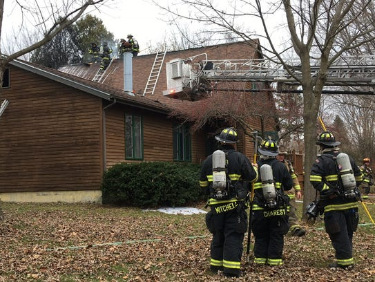 Fire crews work to extinguish a fire at 189 Bacon Drive