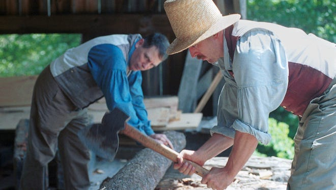 Old Sturbridge Village staff craftsmen Pat Kelly, left, and John Canavan are seen in period costume as they prepare a log for the sawmill, in Sturbridge, Mass., in this June 21, 2000, file photo. This re-creation of a circa 1830 New England village is an educational bonanza for adults and children alike. Interpreters demonstrate dozens of crafts from the period; visitors can take advantage of a full schedule of hands-on learning programs and workshops.