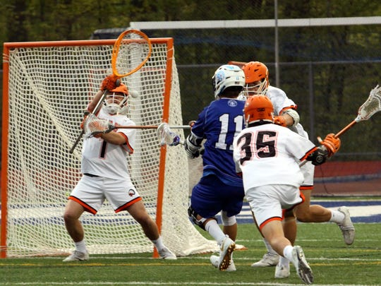 Catholic Central's Peter Thompson (11) takes the shot against Rice goalie Teddy Levois (left) and Michael Cosgrove (35).