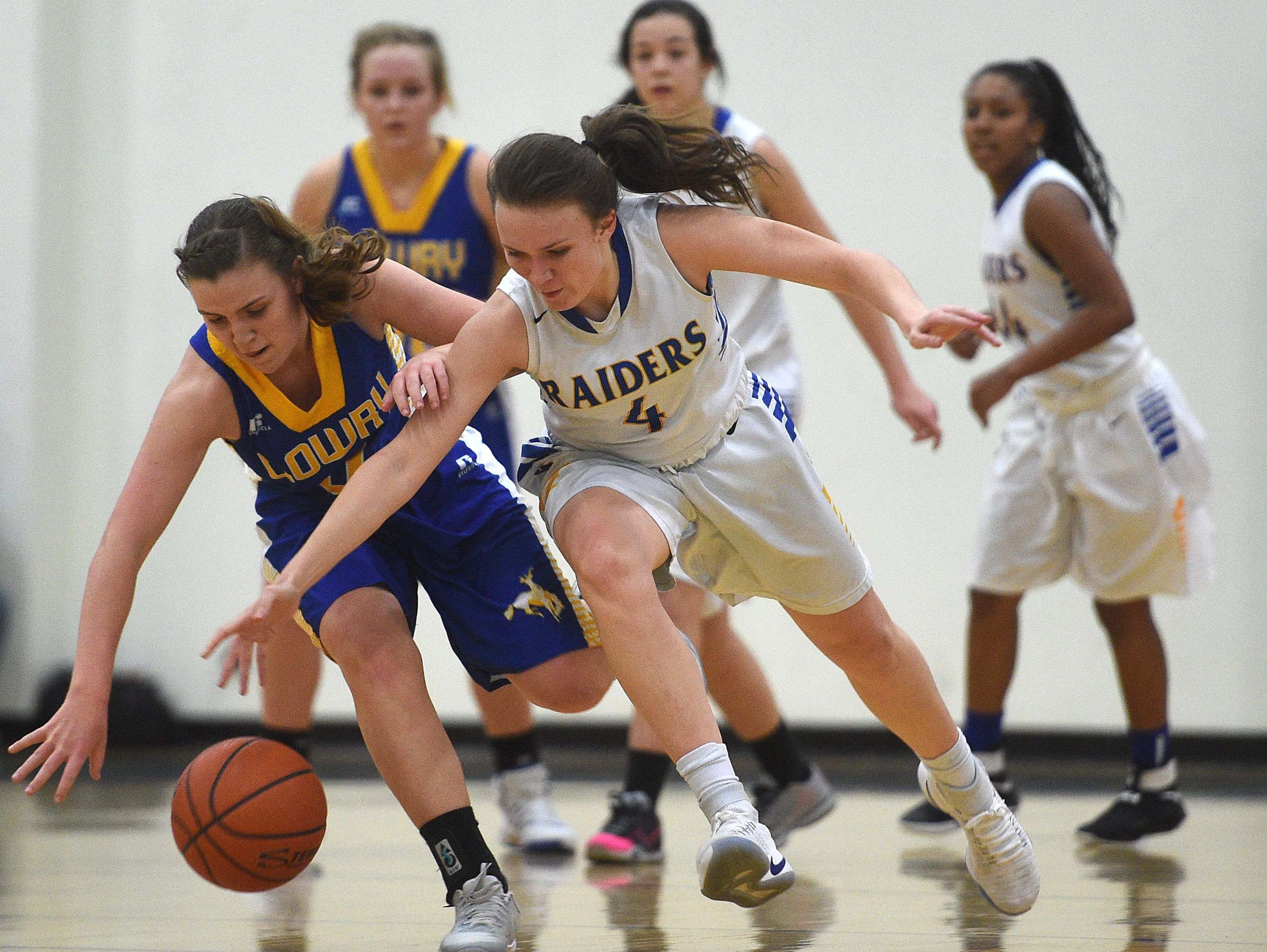 Reed's Taylor Johnson (4) battles Lowry's Sydney Connors for a loose ball during their basketball game Wednesday at McQueen.
