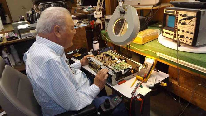 Billy Darnell, founder and former owners of the TV & Radio Clinic in Kingsport, Tenn. works on a VCR/DVD combination unit at the business his son operates. It opened under the Darnells in 1967. (Rick Wagner/The Kingsport Times-News via AP)