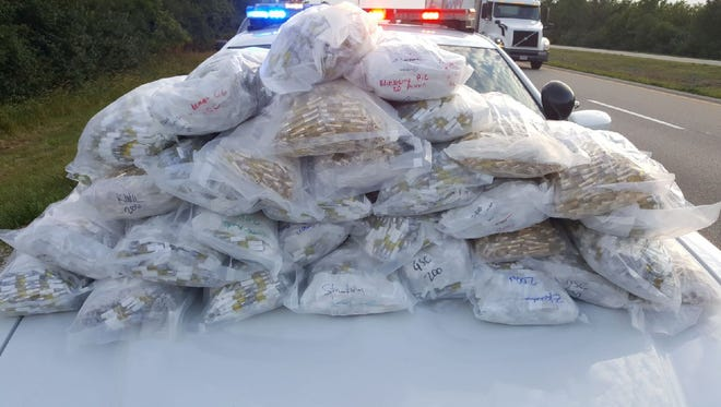 Bags of vaping tubes are piled on a police squad car's hood.