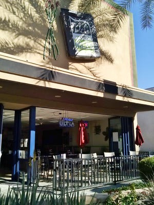 Blue-framed glass doors open onto a patio at Deli on Miles in Indio.