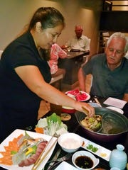 A Shabu-Shabu Zen server demonstrates cooking in broth at a table.