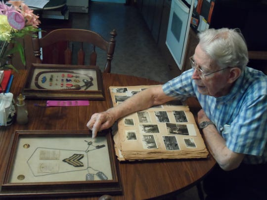 Leon Hyatt Jr. looks at his military memorabilia at his home near Pineville. He was wounded by machine gun fire during World War II, but he returned to battle quickly.