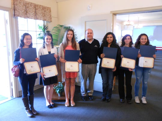 Mission Mortuary presents awards for essay contest.