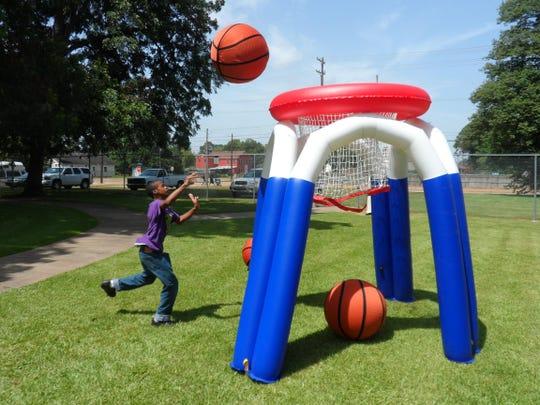 Trevion McCullin shoots an oversized basketball through a hoop during a Rec2U program at Helen Black Park in Alexandria last summer. This summer's Rec2U program begins Tuesday at Harmon Park on Monroe Street.