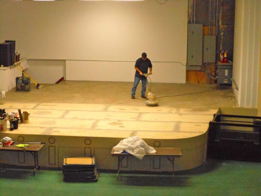 A man sands the new stage built for live performances at the Markay Cultural Arts Center. The renovations for the building took 19 years.