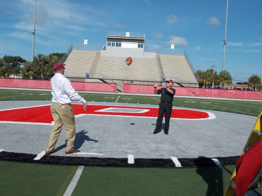 Florida Institute of Technology Athletics Director Bill Jurgens and President and CEO Anthony J. Catanese play catch at midfield.