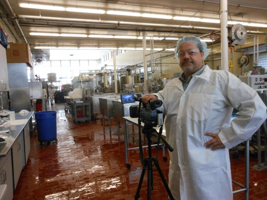 John Mitchell, a producer from California, originally from Cameron Wis., filmed the majority of the documentary on his own. He poses here with his gear during a tour of Babcock Hall Dairy in Madison.