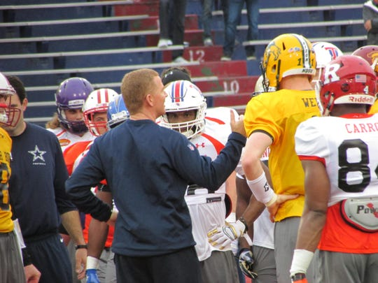 North Dakota State quarterback Carson Lentz (yellow jersey) talks with Dallas Cowboys coach Jason Garrett during Tuesday's practice for the Reese's Senior Bowl.