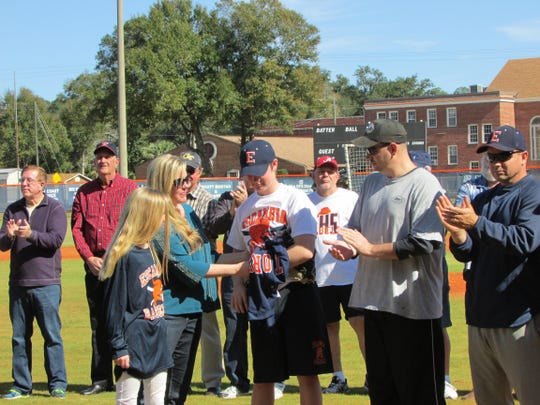Tim Linville's wife and children traveled from Texas to be at Escambia. Mayo presented the jersey Linville wore in the team championship photo. His son, Jackson, a baseball player himself in Texas, threw out the first pitch to start the alumni game. He wore an Escambia uniform.