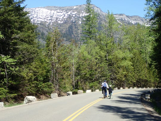 A dad gives his son a lift going up the Going-to-the-Sun Road.