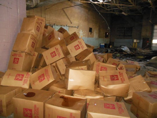A person who worked nearby went into the warehouse and snapped pictures of the boxes, all bearing a red biohazard symbol, before the blaze.