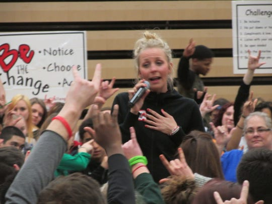 """Hand signs meaning """"I love you"""" surround Flo Luebke as she talks to students Friday at Holt High School. """"All of you are special,"""" she told them."""