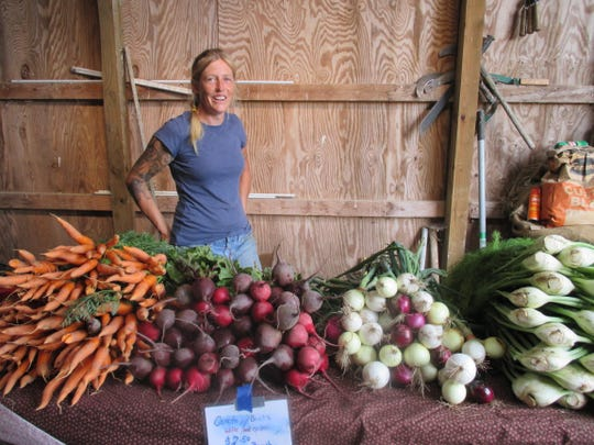 Kira Kinney is shown with a sampling of the organic produce she grows at Evolutionary Organics, her 20-acre farm in New Paltz.